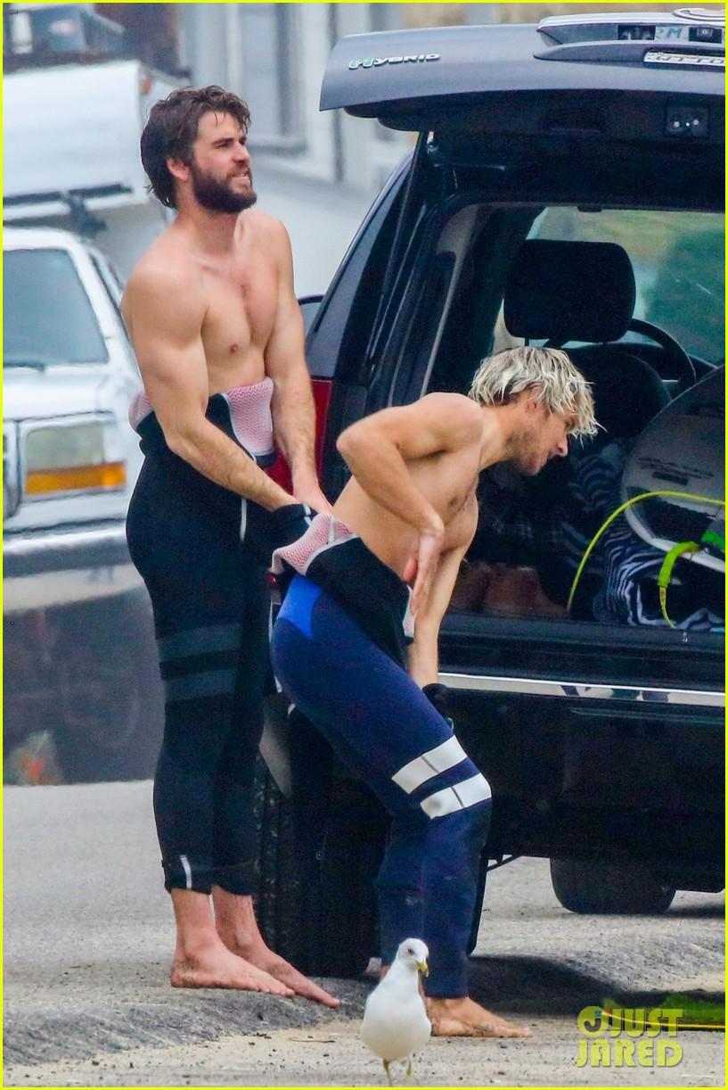 liam hemsworth strips shirtless surfing 01